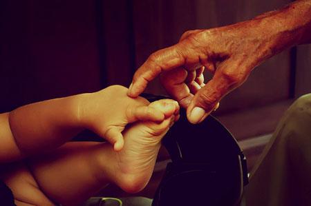 Mano di un nonno che tocca la piccola mano di un bimbo