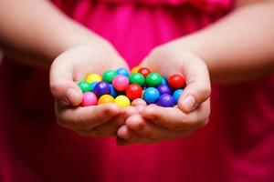 Mani di bimba che tengono biglie colorate