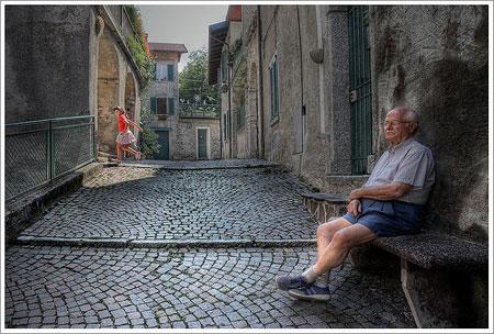 Nonno seduto su panchina di pietra e bimba che gioca tra i vicoli
