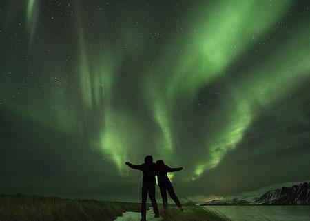 coppia che osserva l'aurora boreale verde