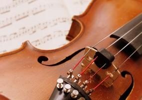 violino in primo piano appoggiato su spartito musicale