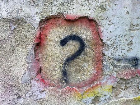 Punto interrogativo disegnato su un muro scrostato