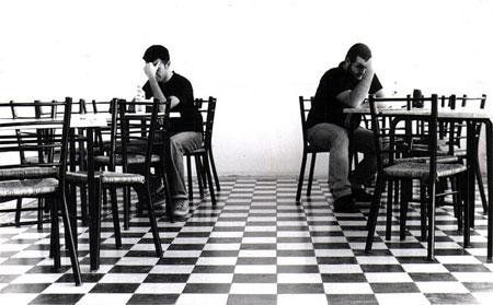 Ragionamento morale due uomini pensierosi seduti in due tavoli diversi